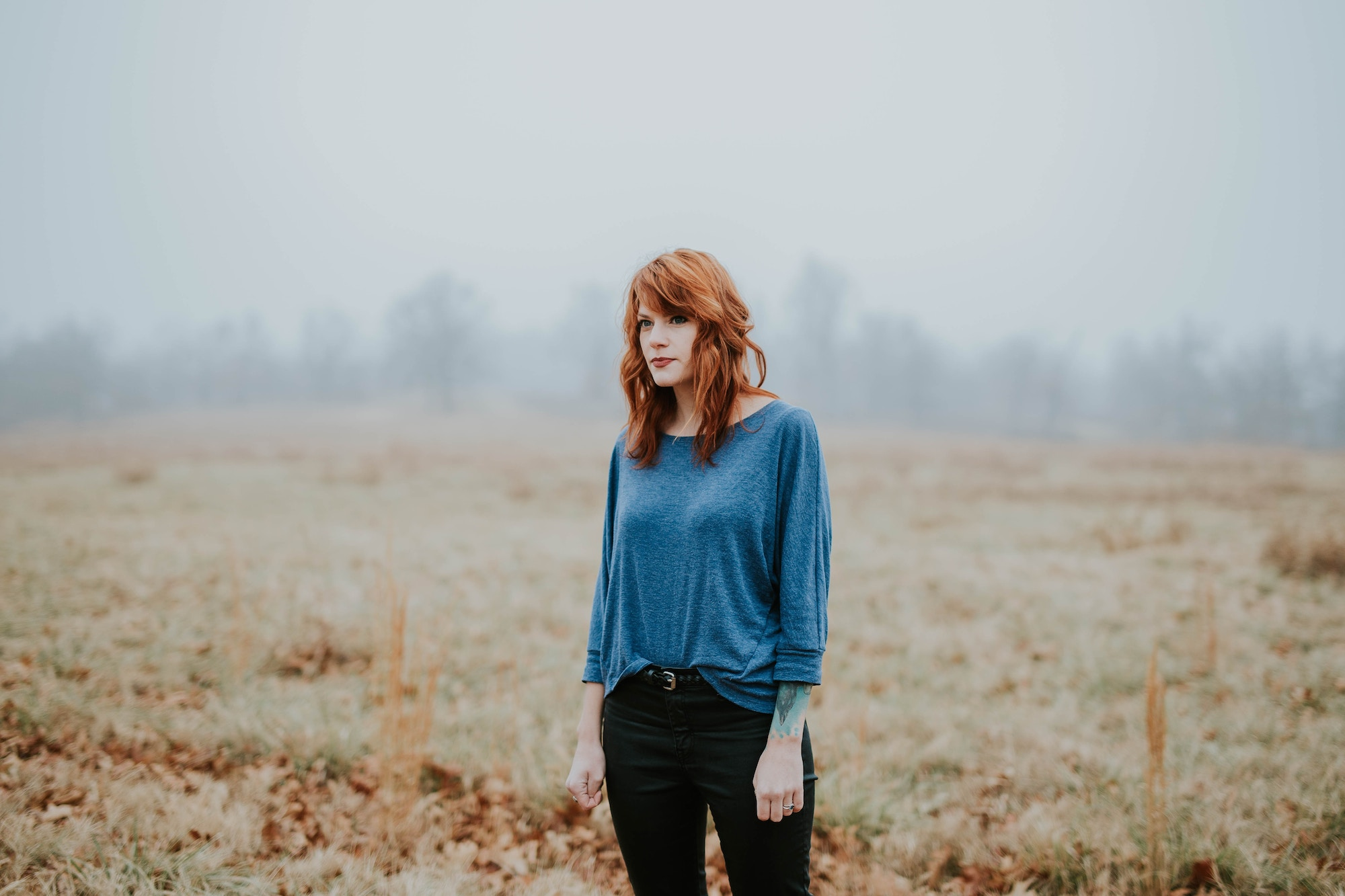 France country life: we tell you what it's like to live in France, like this woman, with red hair, wearing a vibrant blue top, standing in a misty field.