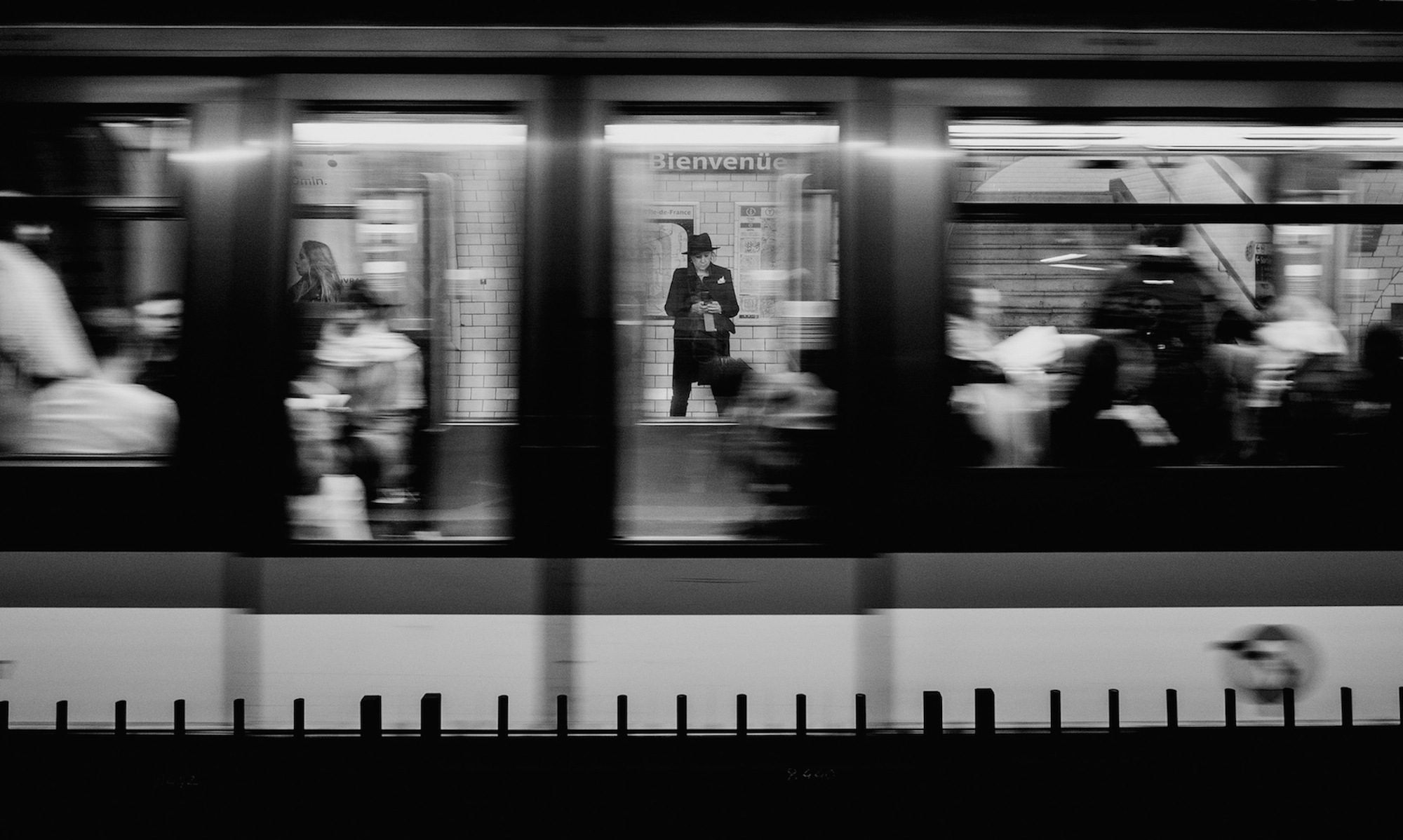 A man stood on a Paris metro platform, seen through the window of a passing metro.