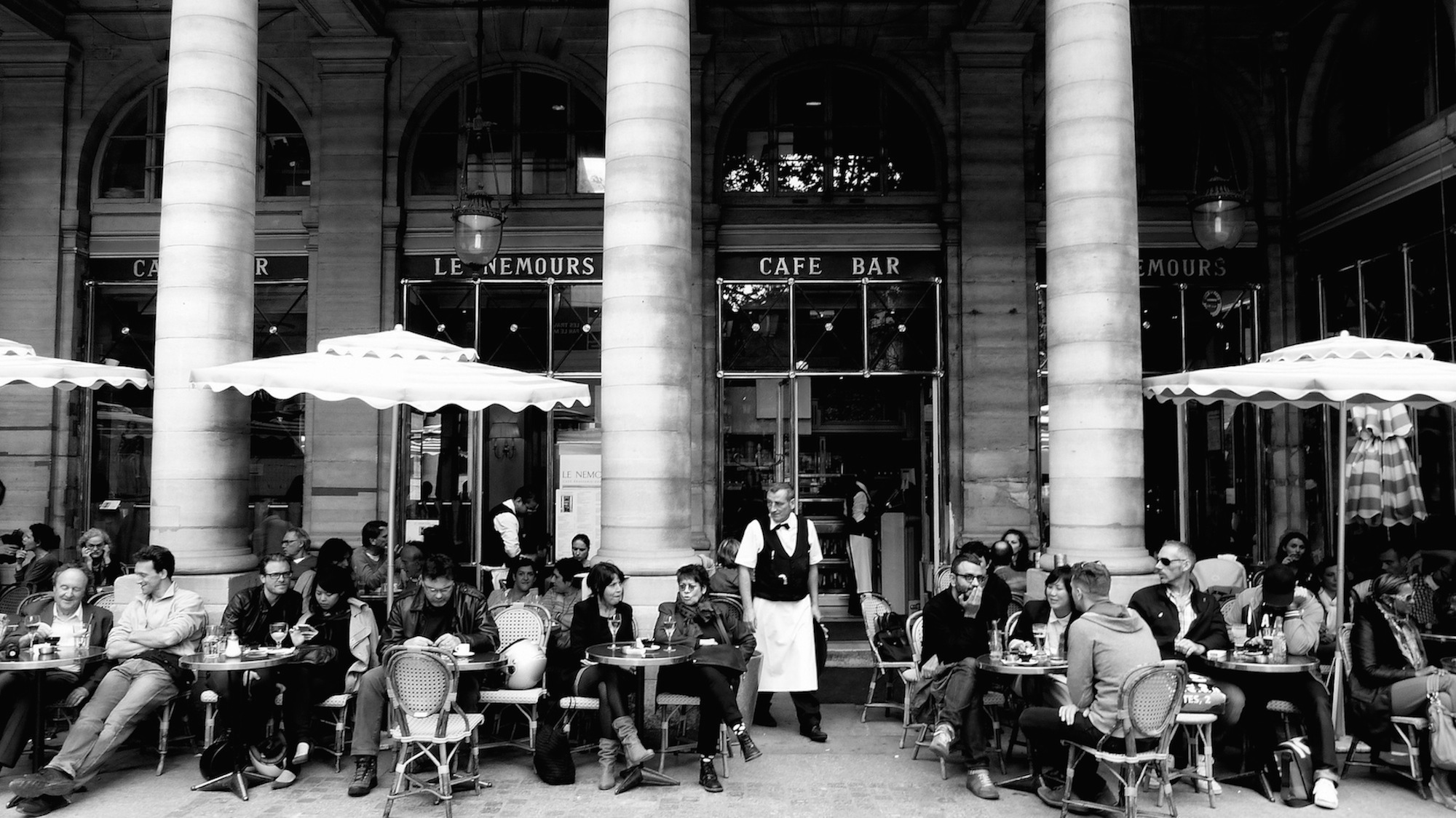 The famous Café Nemours in Paris with people sat having coffee and drinks on the terrace is a great place to listen to people speaking French.