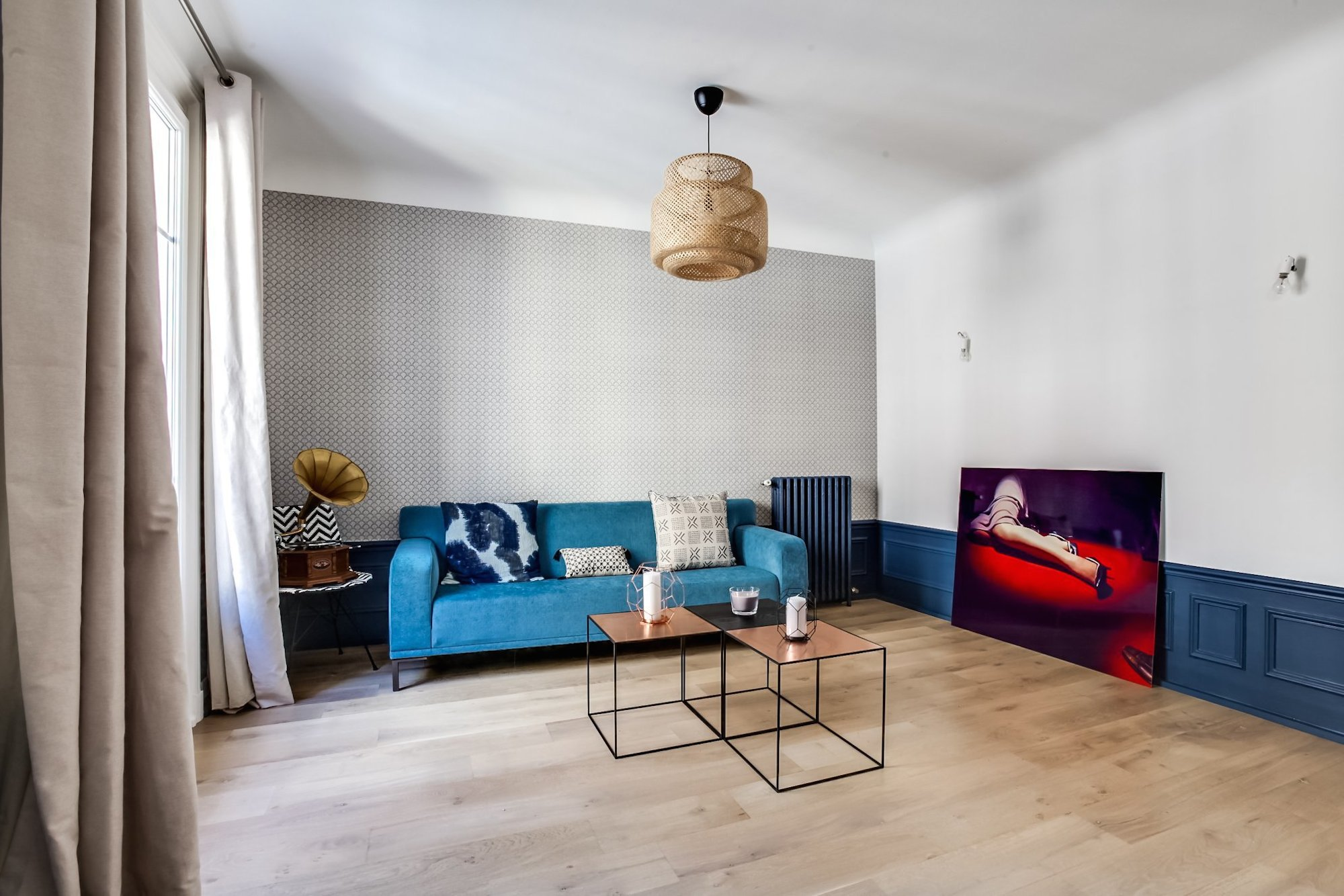 The Foire de Paris home design fair in April in Paris provides great inspiration for your Paris apartment like this one with a blue couch and large artwork of a woman's legs.