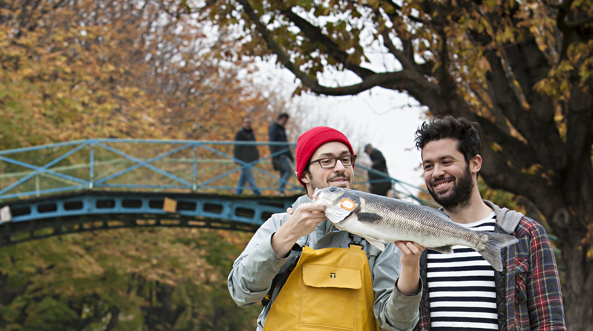 The founders of ethical French fish monger's Poiscaille, on the Canal Saint Martin in Paris, with a fish in hand.