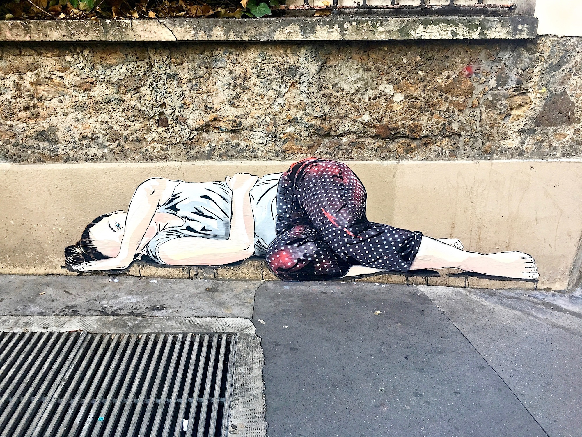 Paris street art also includes a lot of stencil art by artists like Jana und Js, like this piece of a girl lying on the floor.
