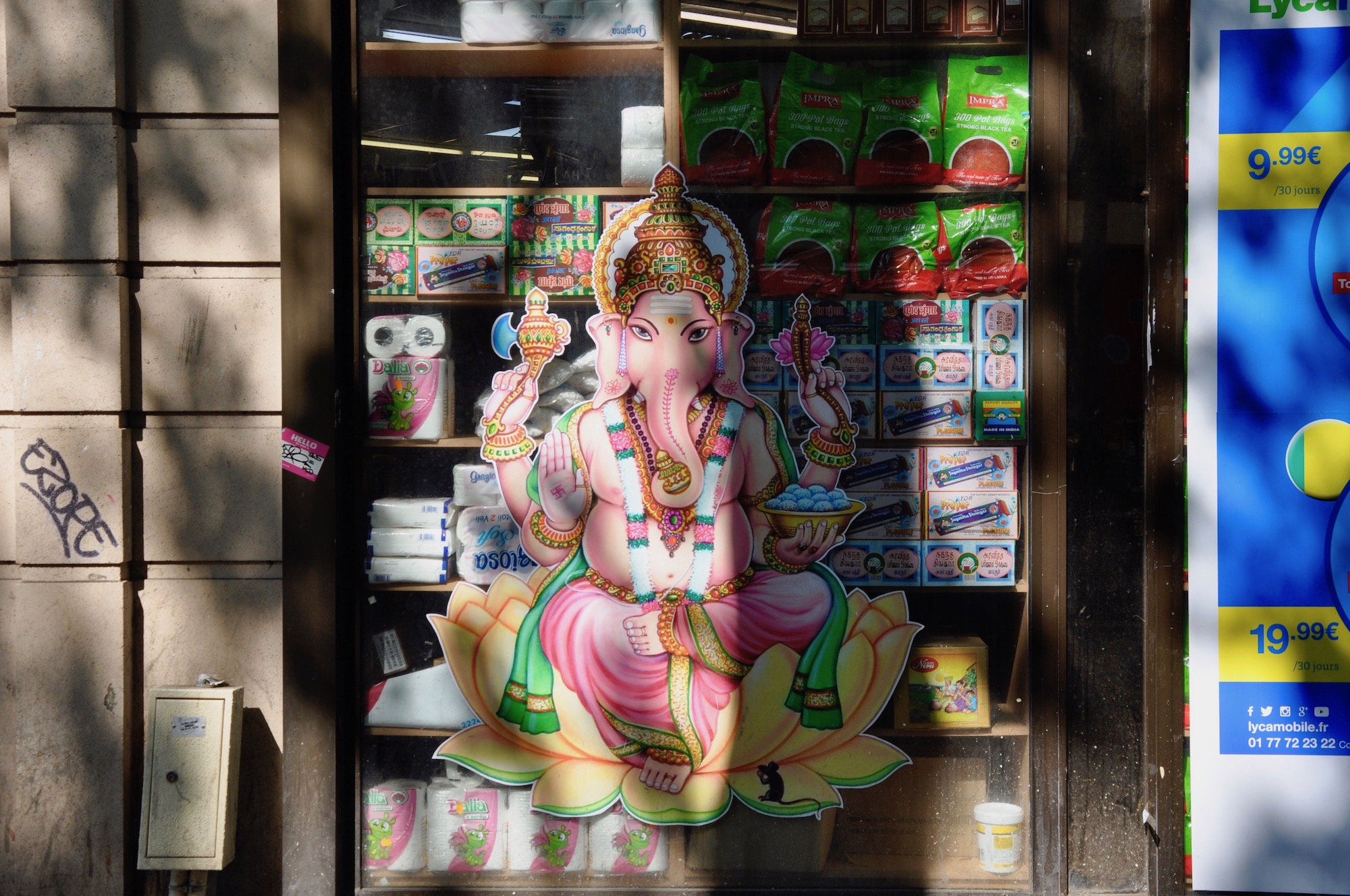 An Indian mini-market with a colorful picture of Ganesh on the window in Indian Paris neighborhood La Chapelle.