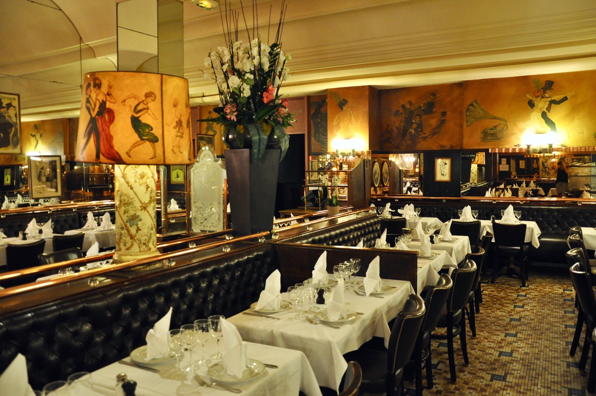Inside the beautiful traditional brasserie Terminus Nord in Paris which serves classic French food, comes with quilted buttoned banquettes, brass fixtures and art on the walls.