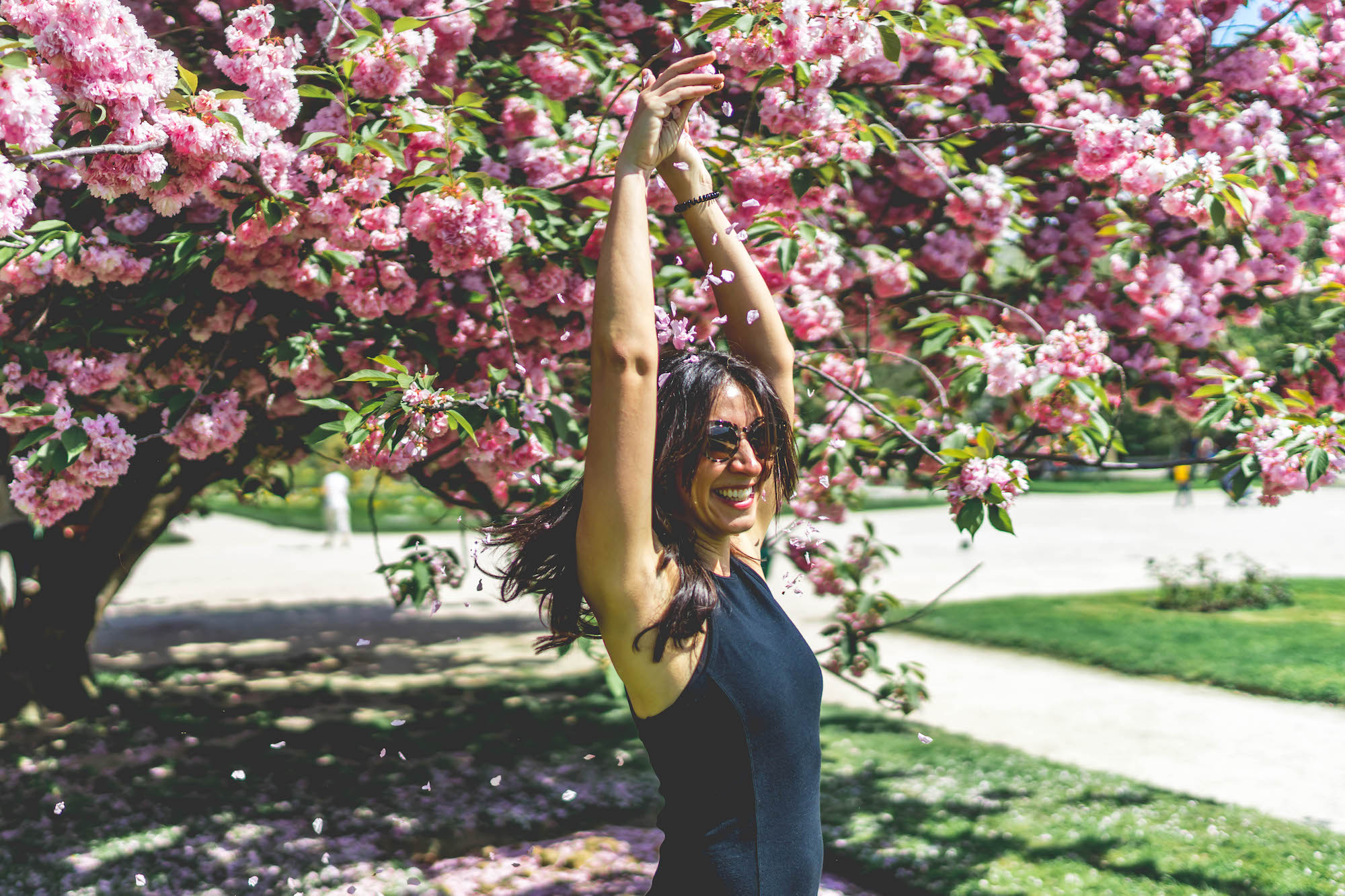 Living in Paris is best in summer when the trees blossom and the city is a wash of pink, which makes you as happy as the woman smiling with her arms up in the air in this picture.