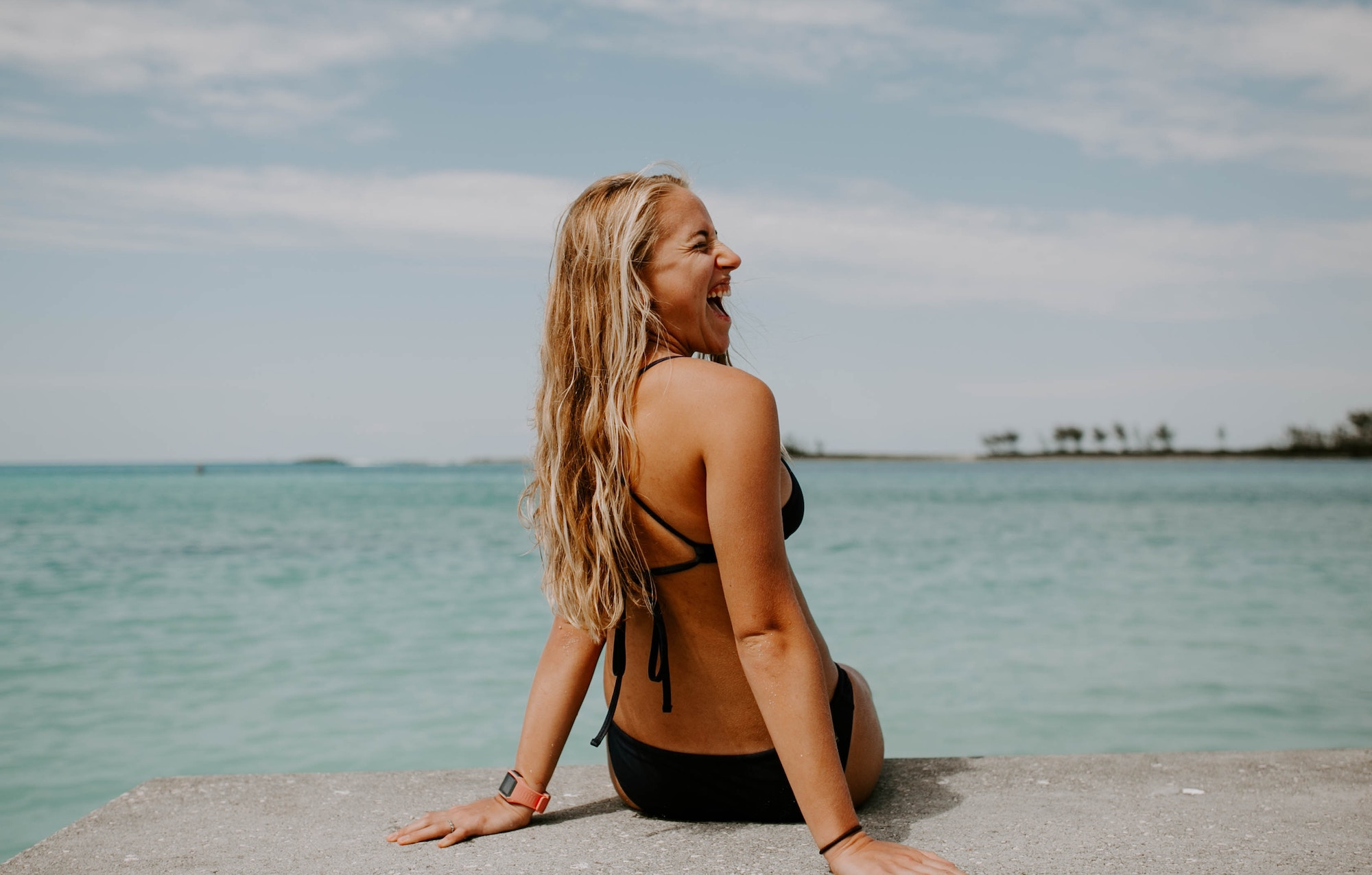 Shopping for a bikini in Pari is not easy but we love this black swimsuit with a crossed back worn by this laughing blonde girl sitting on a concrete slab by the sea.